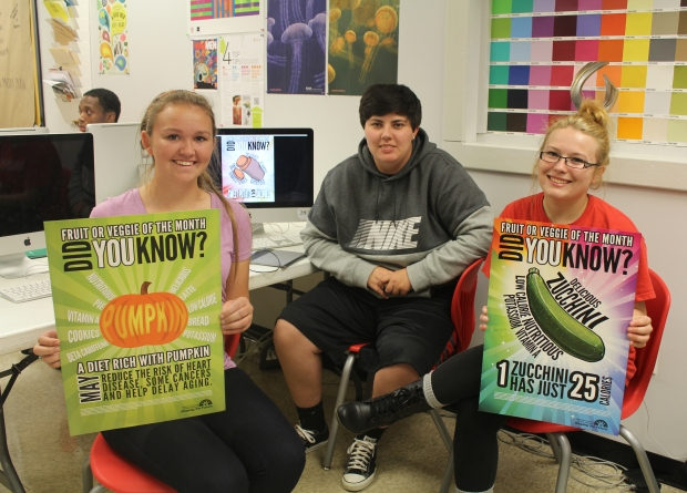[Left to Right] PRP Seniors Kelaiah Clark, Danielle Craft, and Taylor Gray display their designs created for the JCPS Nutrition Services Fruit & Veggie of the Month Campaign.